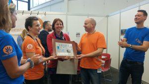 Yvon van SUP-school Domstad overhandigde een donatie die bij elkaar werd gespaard door zwerfafval uit de Utrechtse grachten te vissen.