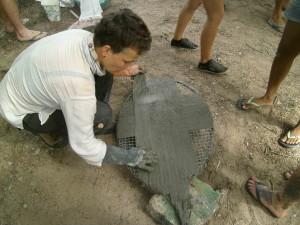 Vera legt uit hoe de lakens met cement om de bladen gemaakt moeten worden.