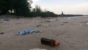 Een glazen fles op het strand.